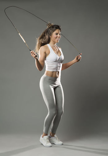 Full Length Of Young Woman Skipping Against White Background