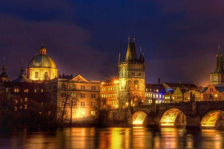 Illuminated charles bridge over vltava river against sky
