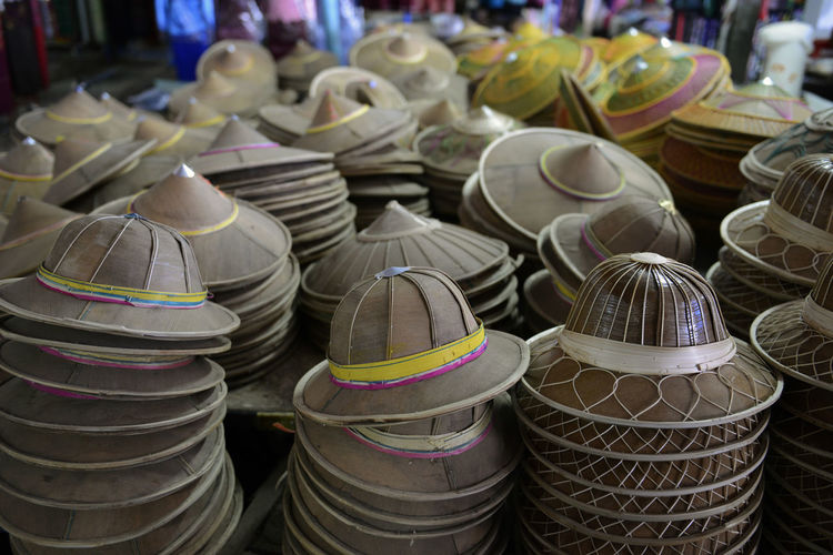 Stack of hats arranged at market for sale