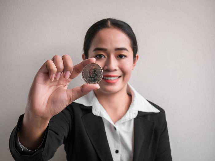 Portrait of smiling businesswoman holding bitcoin while standing against wall