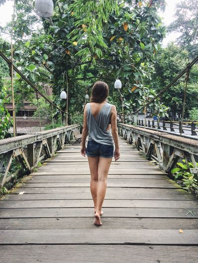 Barefoot Boardwalk Casual Clothing Day Diminishing Perspective Footbridge Full Length Green Color Growth Leading Lines Leisure Activity Lifestyles Outdoors Rear View Scenics Summer The Way Forward Tranquility Tree Ubud Vacation Vanishing Point Walkway Wood - Material Young Women