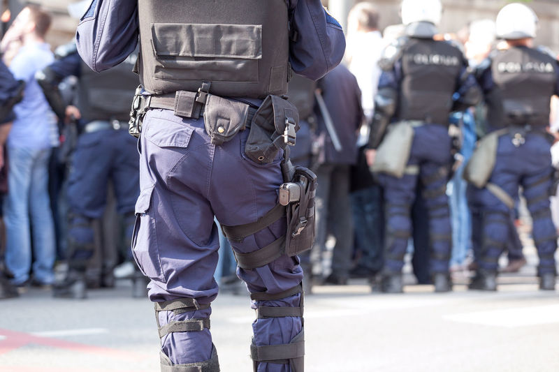 Rear view of police standing on street