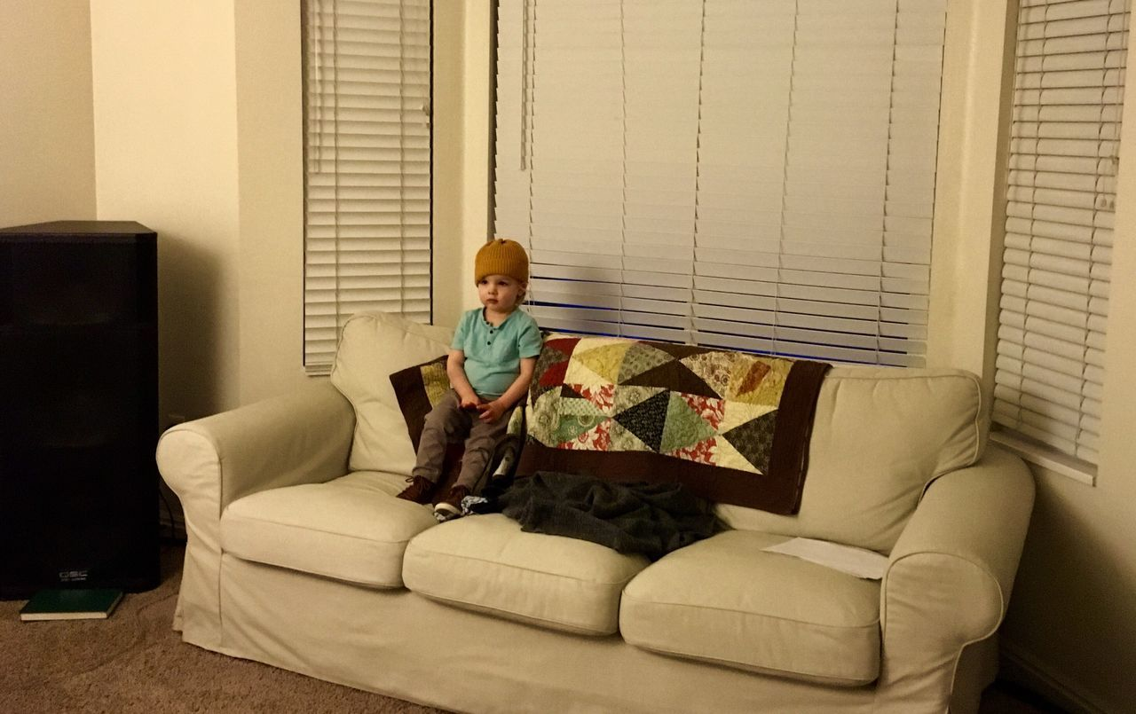 sofa, indoors, living room, home interior, one person, full length, real people, lifestyles, childhood, domestic life, leisure activity, boys, casual clothing, elementary age, holding, sitting, learning, day, people