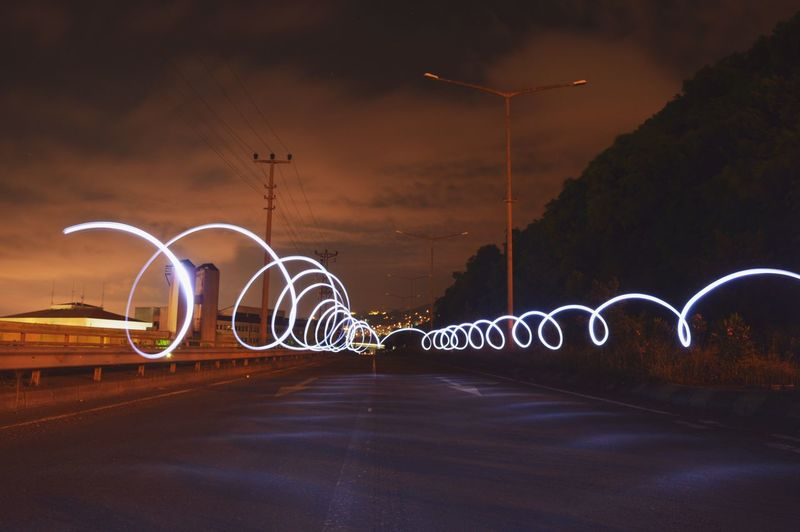 Illuminated light painting on road against sky at night