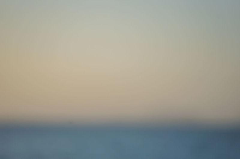Defocused image of sea against clear sky