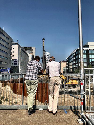 Rear view of men standing against buildings in city