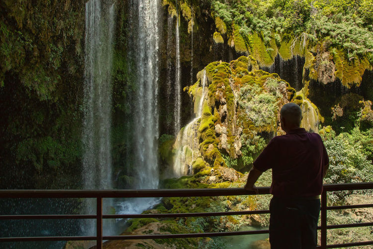 Rear View Of Man Standing At Observation Point Against Waterfall