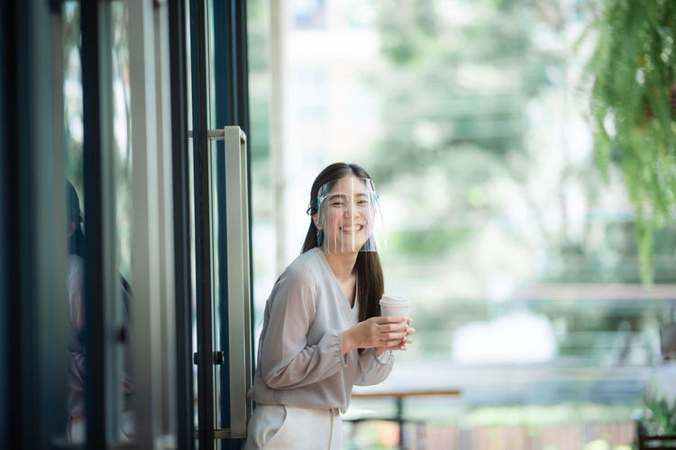 Portrait of a smiling young woman holding glass window