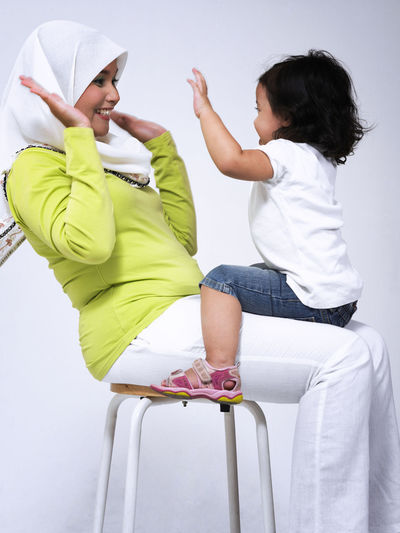 Side View Of Playful Mother And Daughter Sitting On Seat Over White Background