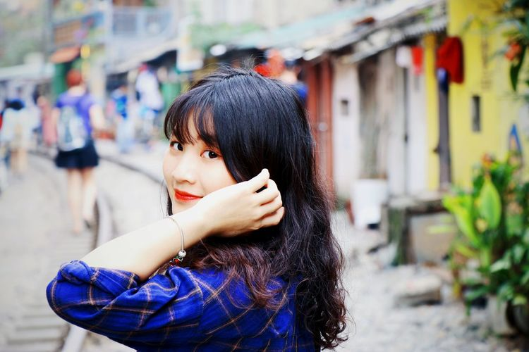 Side view portrait of smiling young woman in town