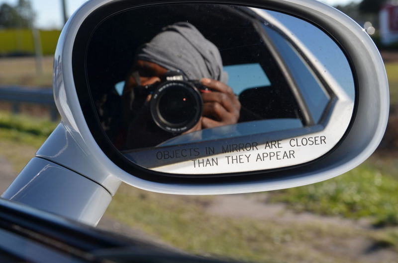 Reflection Of Man Photographing Through Camera In Side-View Mirror