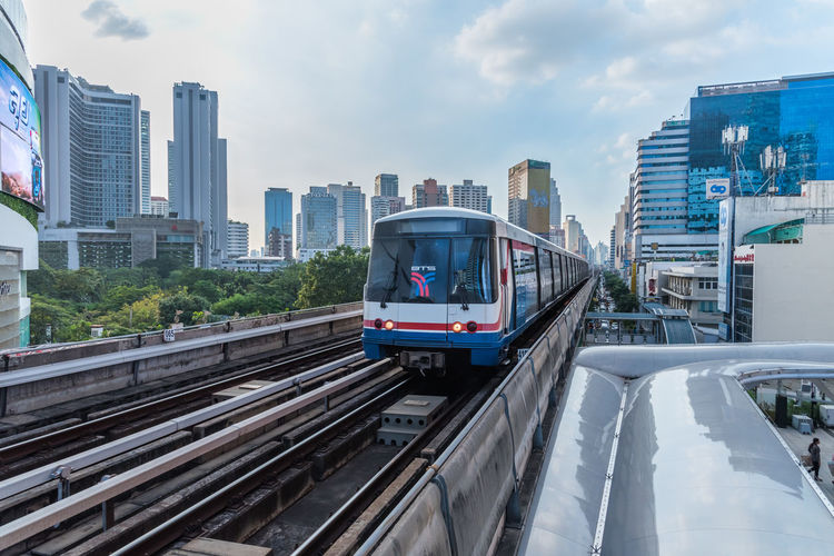 Train on railroad tracks amidst buildings in city against sky