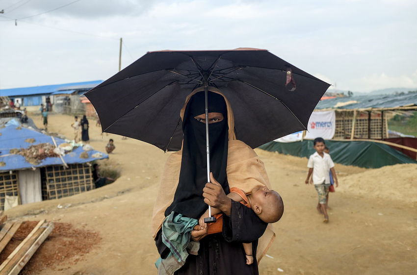 A Rohingya mother carries her child at Kutupalong Refugees Camp near Coxs bazar Bangladesh Rohingya Adult Building Exterior Child Childhood Cloud - Sky Day Holding Incidental People Leisure Activity Lifestyles Males  Men Nature Outdoors People Protection Rain Real People Sky Umbrella Women The Portraitist - 2018 EyeEm Awards The Photojournalist - 2018 EyeEm Awards The Traveler - 2018 EyeEm Awards EyeEmNewHere