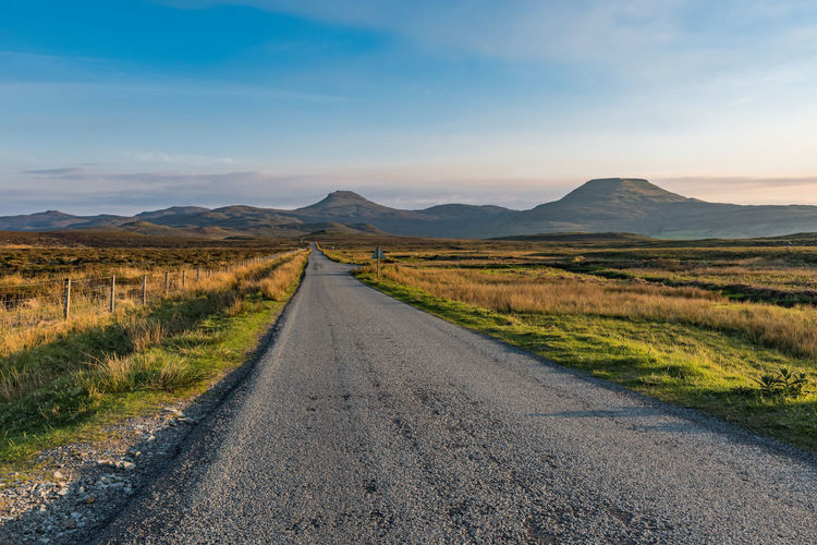 A straight, narrow and empty tarmac road meets at the horizon with the mountains at the isle of sky