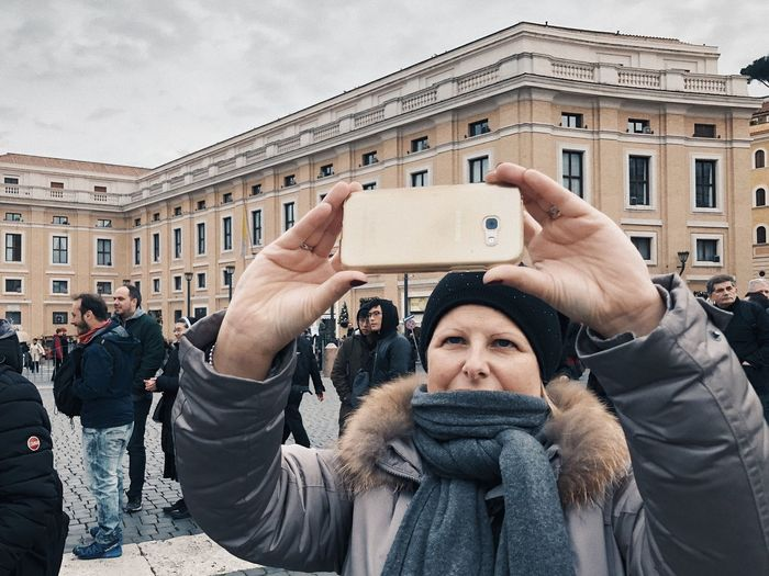 Portrait of young woman photographing in city