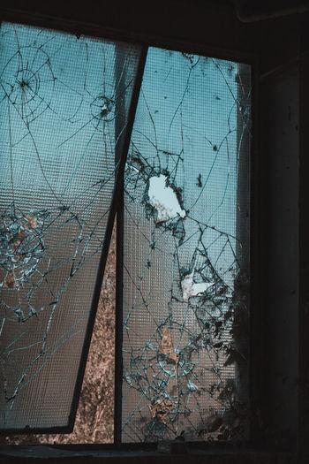 Broken glass window of abandoned building