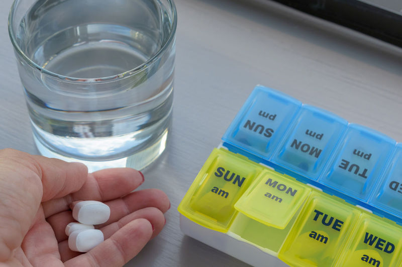 Close-up of woman hand holding pills by box and glass of water