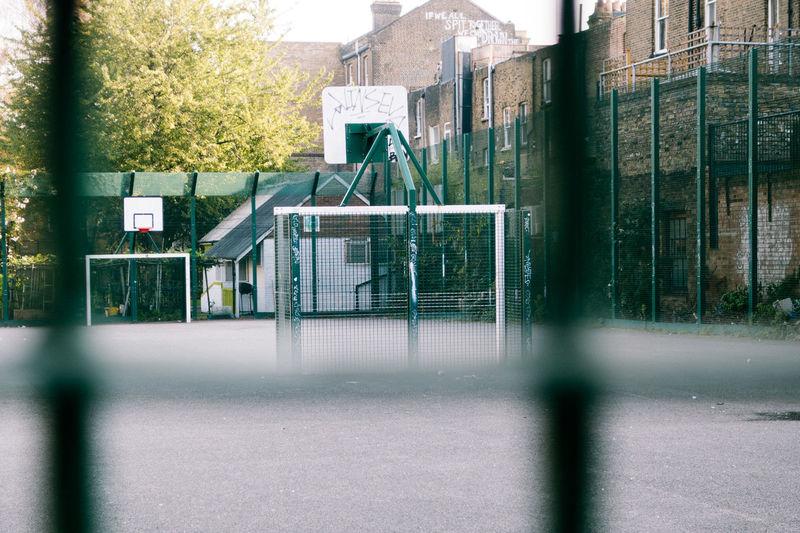 Empty Basketball Court Seen Through Fence