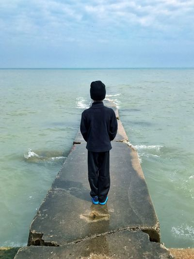 What do you see? Big Bay Park Big Bay Beach Milwaukee, Wisconsin Pier Water Pier Concrete Rear View Child Young Boy Blue Color Lake Lake Michigan Waves Horizon Over Water