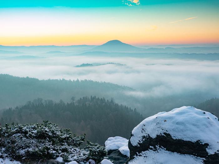Scenic view of snow covered mountains against sky during sunset