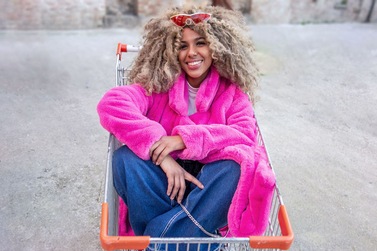 Portrait of a young african American woman smiling inside a shopping cart. Sitting Smiling Happiness Women One Person Emotion Casual Clothing Adult Portrait Young Adult Looking At Camera Hair Beautiful Woman Pink Color Warm Clothing Hairstyle Clothing Front View Lifestyles Females Cheerful African Descent Afro-american African American Afro American Girl Beauty In Nature Shopping Cart Inside Indoors  Cheerleading Cheerleader Fun Playing Blonde Curly Hair Afro Hair Mall Supermarket