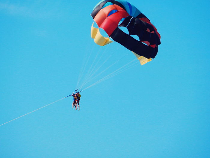 Low angle view of parachuting against clear blue sky