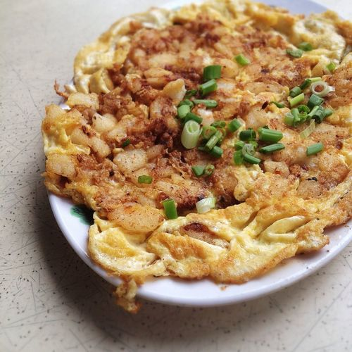Omelet with potatoes and scallion in plate