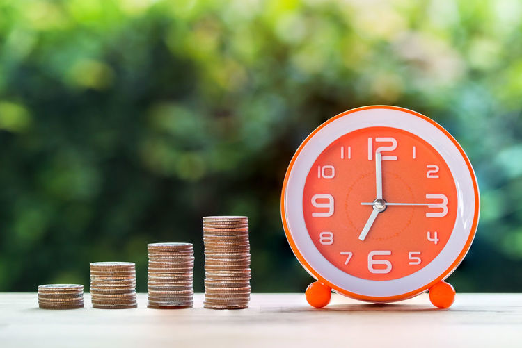 Close-up of alarm clock and stacked coins on table