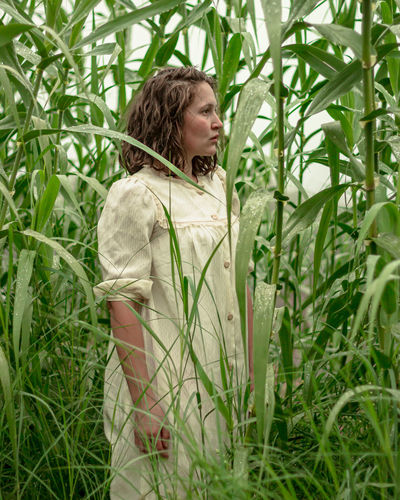 Woman looking away from camera while standing in field