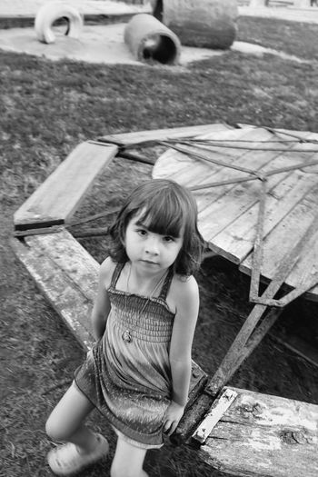 High angle portrait of girl sitting on merry-go-round at playground