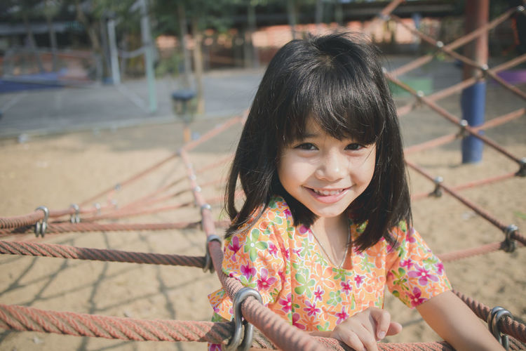 Portrait of smiling girl on jungle gym in park