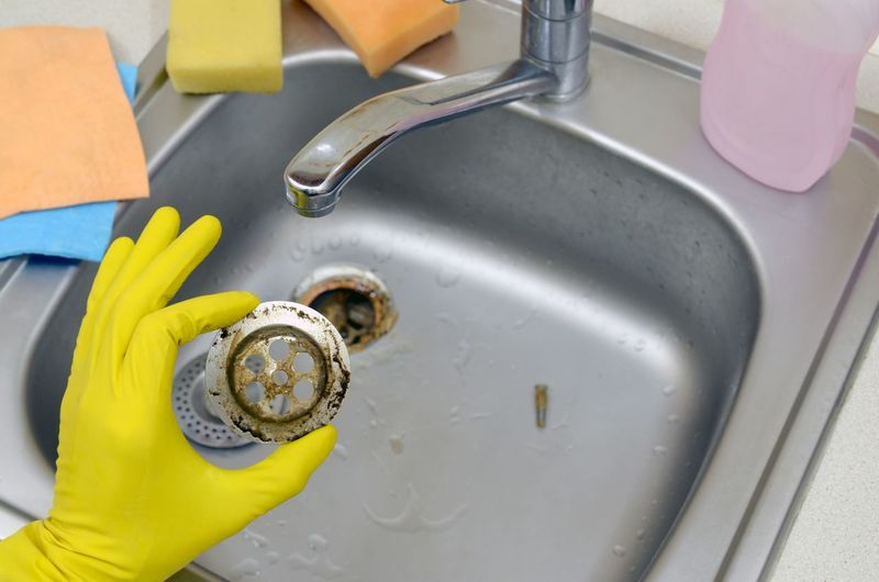 Cropped image of person cleaning sink