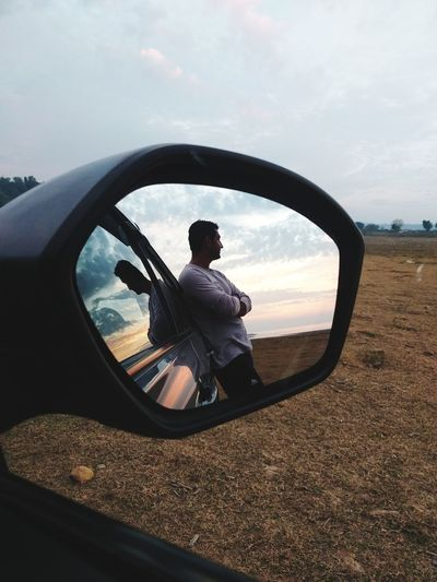 Reflection of man on side-view mirror