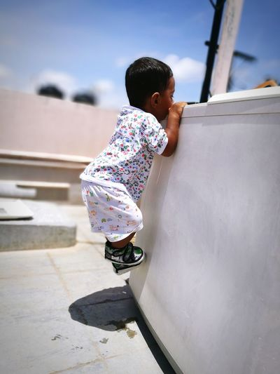 Toddler boy climbing on structure