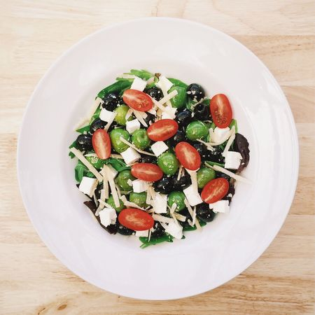 Green olive, tomato and cheese salad Green Olives Tomato Cheese Leaves Salad Healthy Diet White Plate Healthy Food Olive Oil