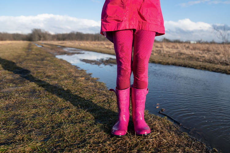 Young girl wearing pink wellie rainboots standing near a muddle puddle in spring
