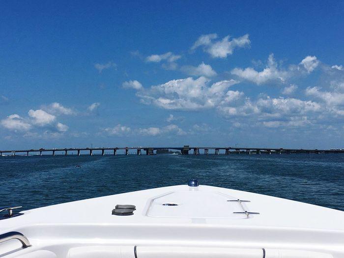 Boat Sailing In Sea By Bridge Against Sky