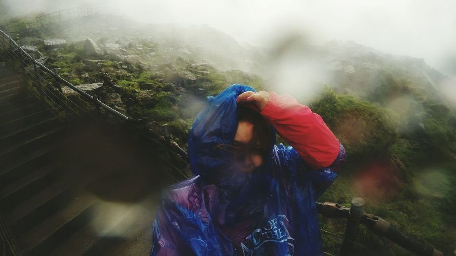 Close-up of woman wearing raincoat while standing on staircase during rainy season