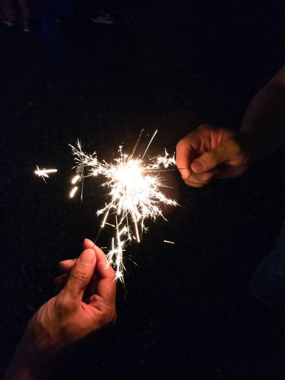 Close-up of hand holding sparkler at night