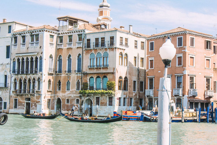 Gondolas moored in grand canal by buildings