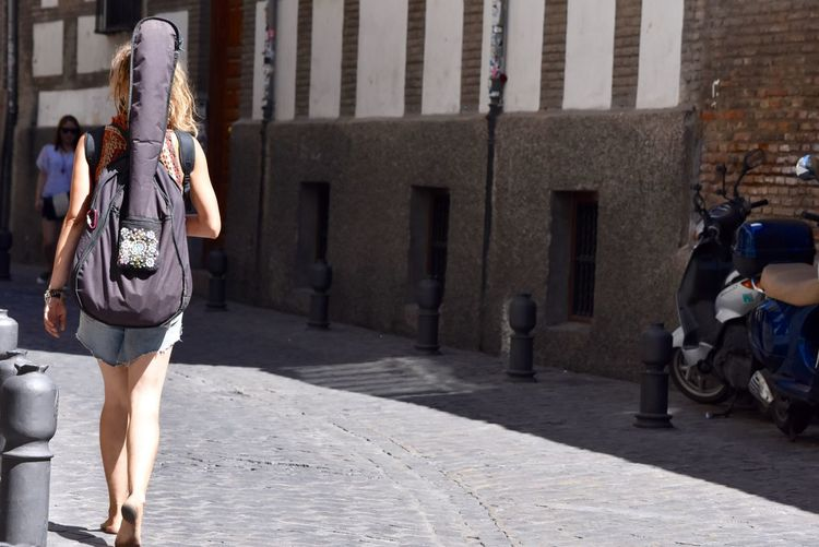 Rear view of woman with guitar walking on street