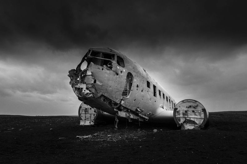 Damaged Airplane On Field Against Cloudy Sky
