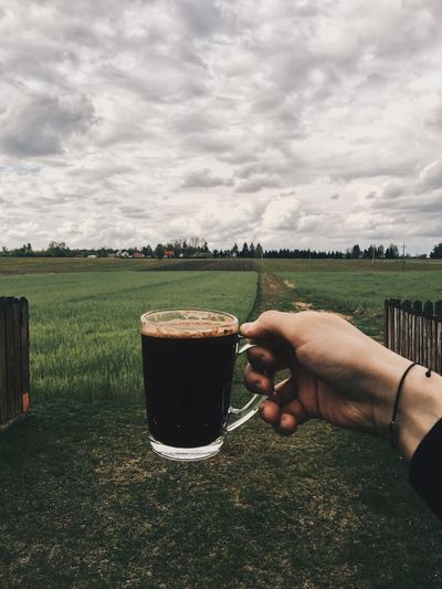 Hand holding coffee cup on land
