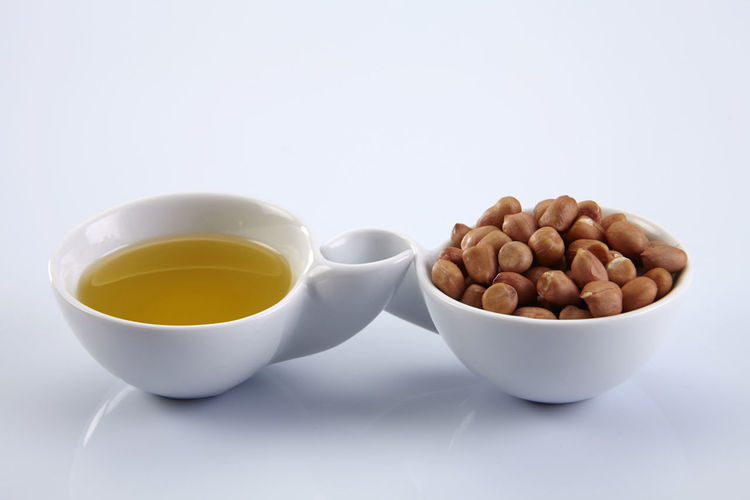 bowl of peanut cooking oil and bowl full of peanuts side by side Peanut Peanuts Groundnut Dried Food Healthy Eating Cooking Oil Oil Saucer Bowl Container Side By Side Yellow Golden Food And Drink Food Cup Wellbeing Freshness White Background Indoors  Studio Shot Still Life Crockery Close-up No People