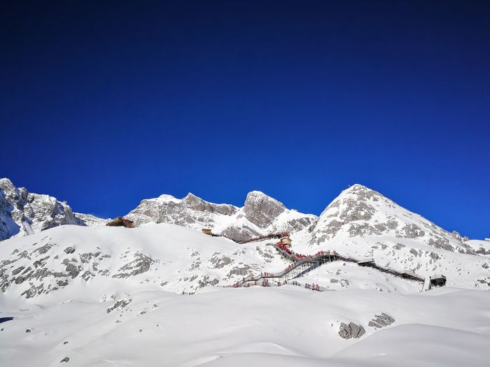 Scenic view of snowcapped mountains against clear blue sky jade dragon snow mountain
