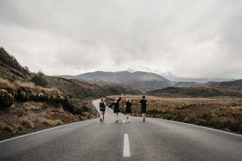 Friends running on road against sky