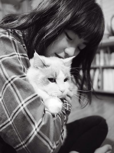 Close-up of teenage girl with cat sitting at home