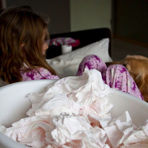 Tissues By Girl Lying In Bedroom