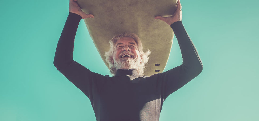 Low angle view of cheerful man carrying surfboard against clear sky