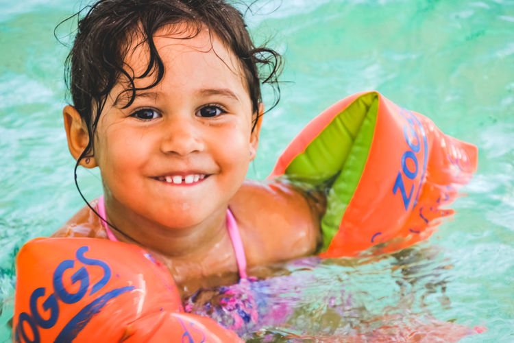 portrait of a happy little girl in a swimming pool wearing floaties Child Childhood Water Smiling Portrait Happiness Swimming Pool Pool Leisure Activity One Person Swimming Emotion Looking At Camera Headshot Cheerful Real People Enjoyment Innocence Outdoors Inflatable  Floating On Water Girls Toddler